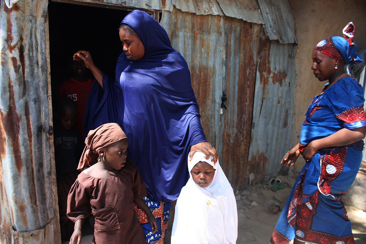 Falmata Gana, widowed after members of the Islamist sect Boko Haram killed her husband in 2012, walks out of the small room she shares with 11 children. Maiduguri, northeastern Nigeria. Photo by Chika Oduah. December 17, 2014